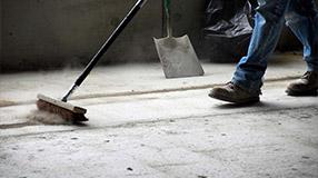 Gebäudereinigung JWeber Person macht eine Baureinigung mit einem Besen